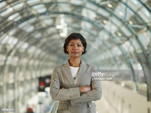 african businesswoman standing with arms crossed - bogen architektonisches detail stock-fotos und bilder