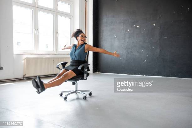 african businesswoman taking a break in the office and rolling on the office chair - friday stock pictures, royalty-free photos & images