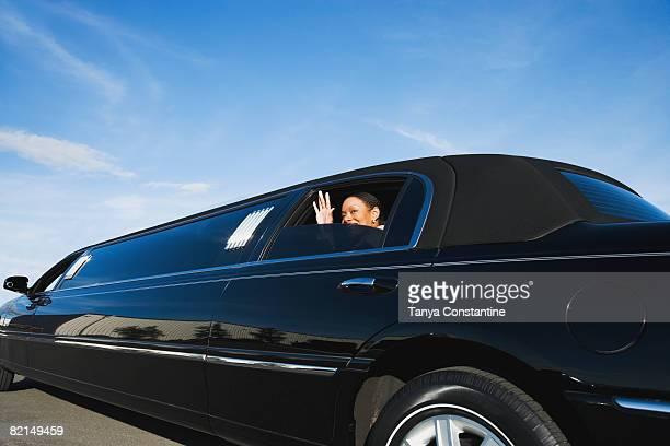 african businesswoman waving from limousine - tanya constantine stock pictures, royalty-free photos & images