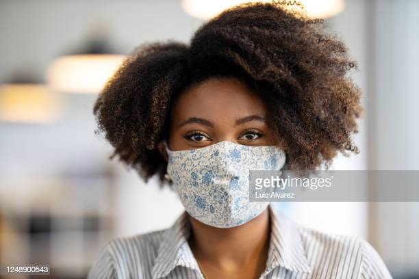 african businesswoman with face mask in office - women stock pictures, royalty-free photos & images