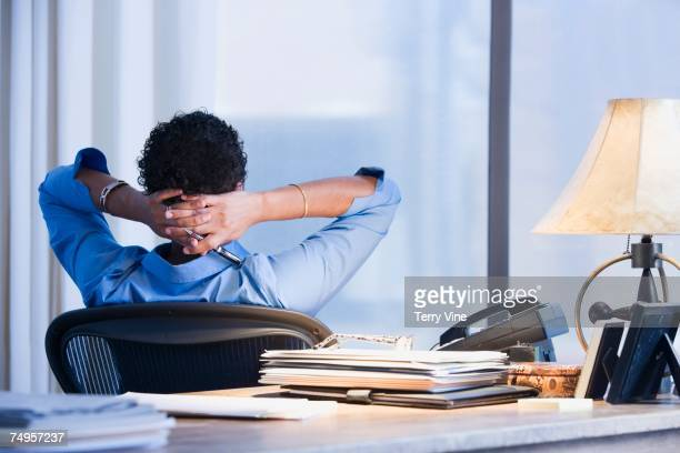 African businesswoman with hands behind head