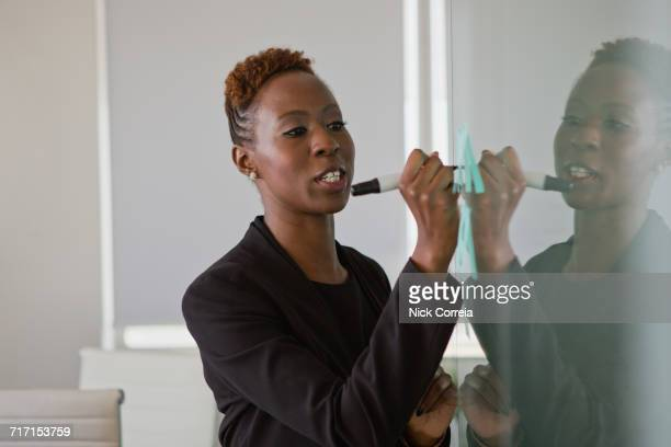 African businesswoman writing on adhesive note at office