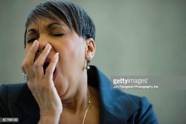 African businesswoman yawning