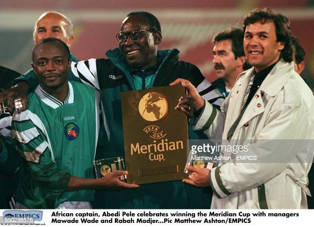 African captain Abedi Pele celebrates winning the Meridian Cup with managers Mawade Wade and Rabah Madjer
