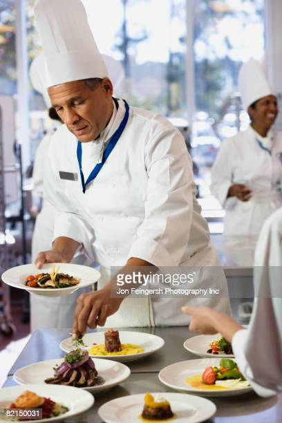 African chef garnishing plate of food
