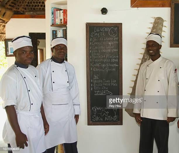 African chefs next to menu in restaurant