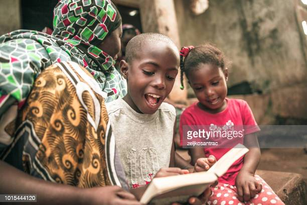 african child doing her homework with her mother - africa stock pictures, royalty-free photos & images