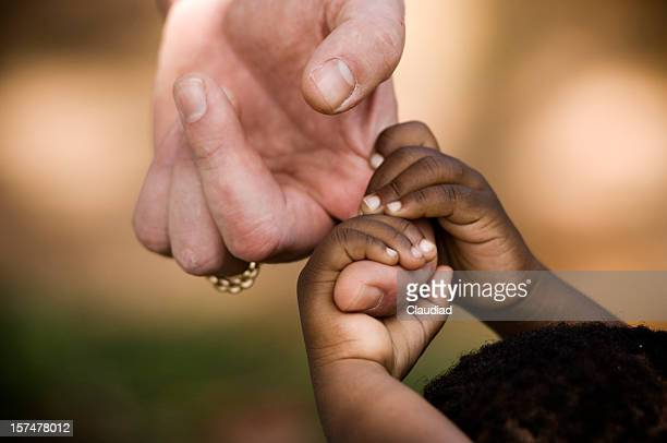 african child grabbing the hand of a man - adoptie stockfoto's en -beelden