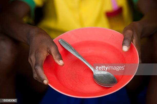 african child holds empty plate - hungry stock pictures, royalty-free photos & images