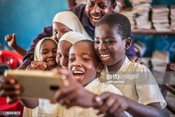 african child  taking selfie in classroom - east africa stock pictures, royalty-free photos & images