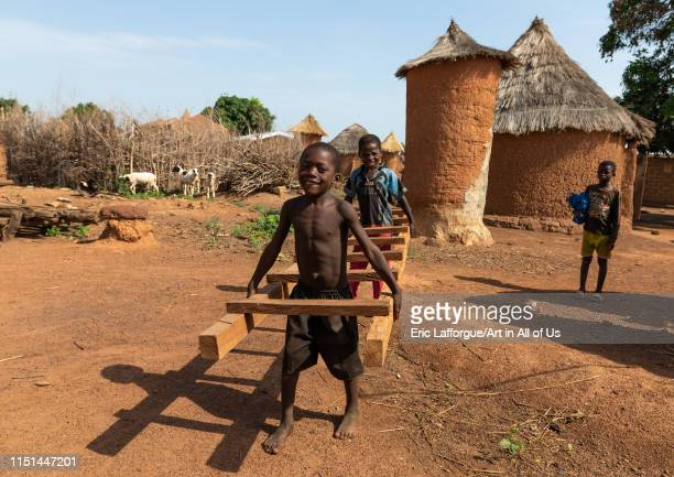 African children carrying a ladder in front of granaries, Savanes district, Niofoin, Ivory Coast on May 3, 2019 in Niofoin, Ivory Coast.
