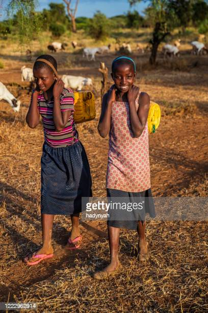african children carrying water from the well, kenya, east africa - east african tribe stock pictures, royalty-free photos & images