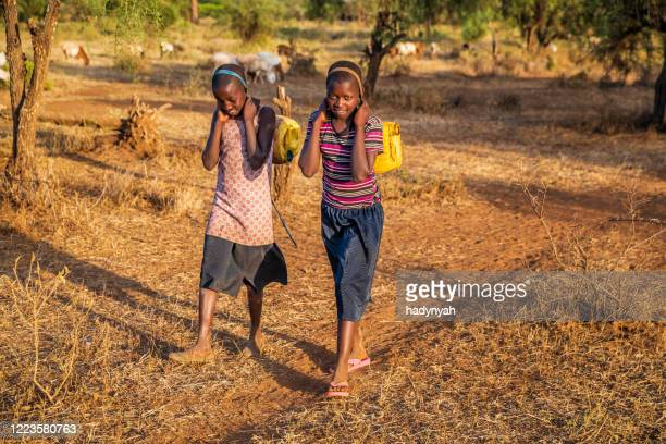 african children carrying water from the well, kenya, east africa - native african girls stock pictures, royalty-free photos & images