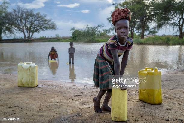 African children filling up water containers from a small muddy dam