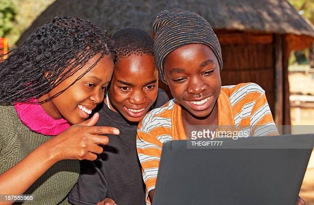 Enfants africains à la recherche à un ordinateur portable