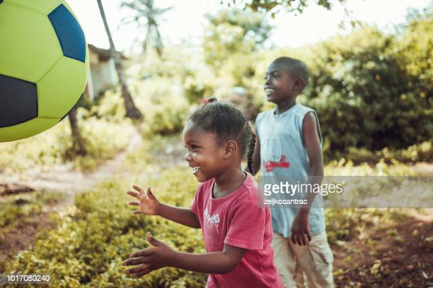 african children playing football in the village - poor africans stock pictures, royalty-free photos & images