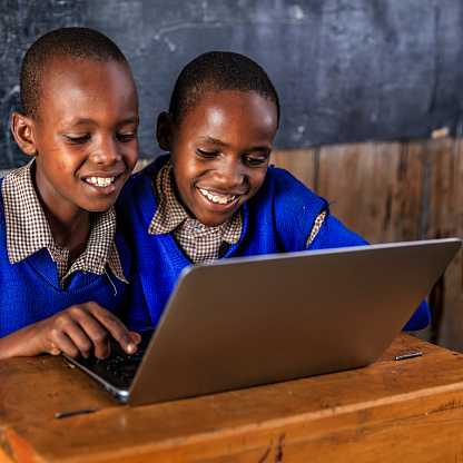 African children using a laptop inside classroom, Kenya 610137520