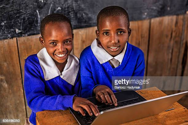 African children using a laptop inside classroom, Kenya
