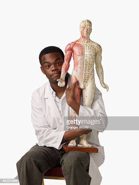 African chiropractor holding anatomical model