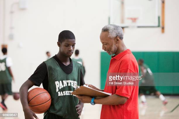 African coach and basketball player reviewing plays in gym