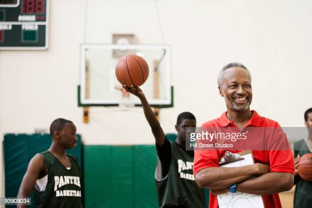 African coach and basketball players in gym