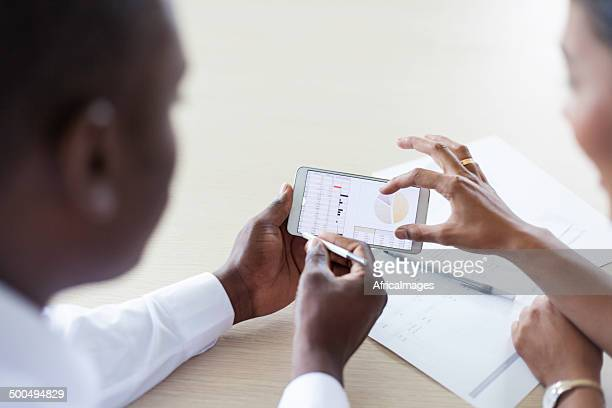 African colleagues looking at a spread sheet on a cellphone