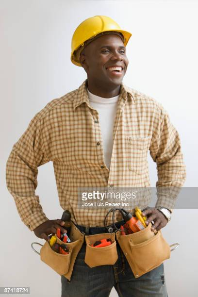 African construction worker in hard-hat and tool belt