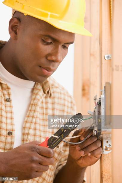 African construction worker in hard-hat wiring lightswitch