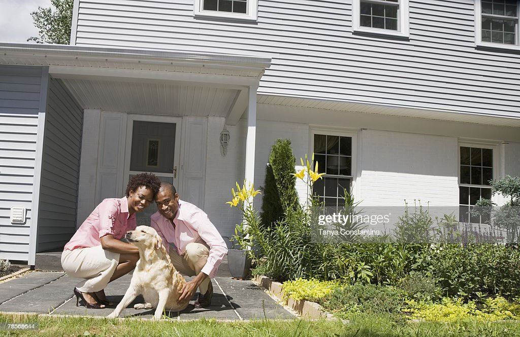 African couple and dog in front of house : Stock Photo