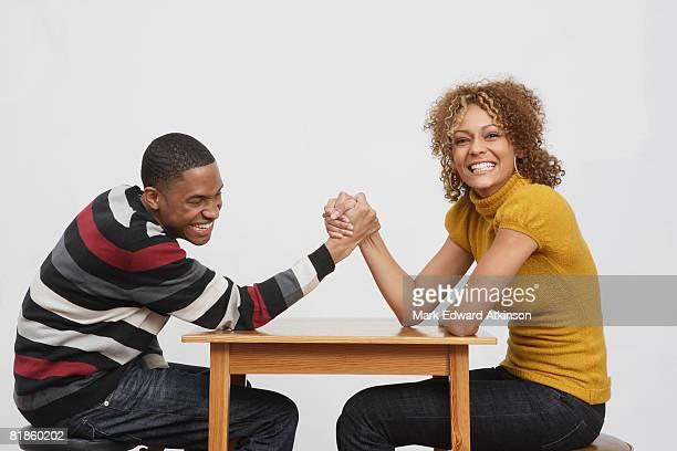 african couple arm wrestling - 男女の争い ストックフォトと画像