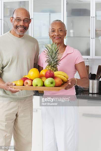 african couple holding tray of fruit - heterosexuelles paar stock-fotos und bilder