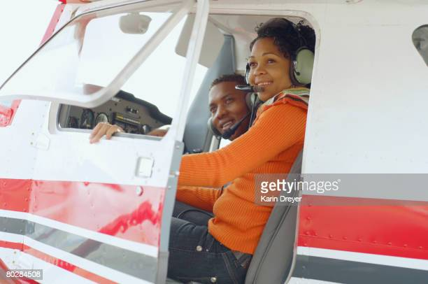 African couple in cockpit of airplane
