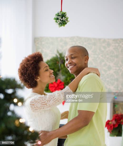 african couple kissing underneath mistletoe - mistletoe stock photos and pictures