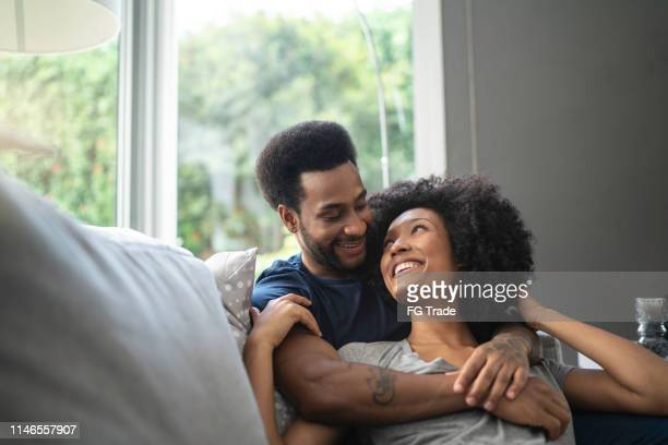 african couple lying down and having romantic moment on couch - boyfriend stock pictures, royalty-free photos & images