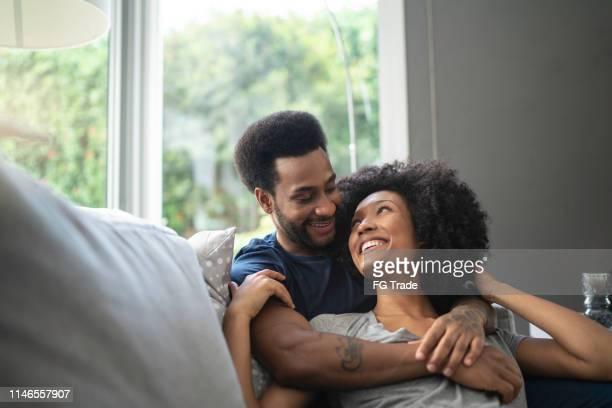 couples africains couchés et ayant le moment romantique sur le divan - petit ami photos et images de collection