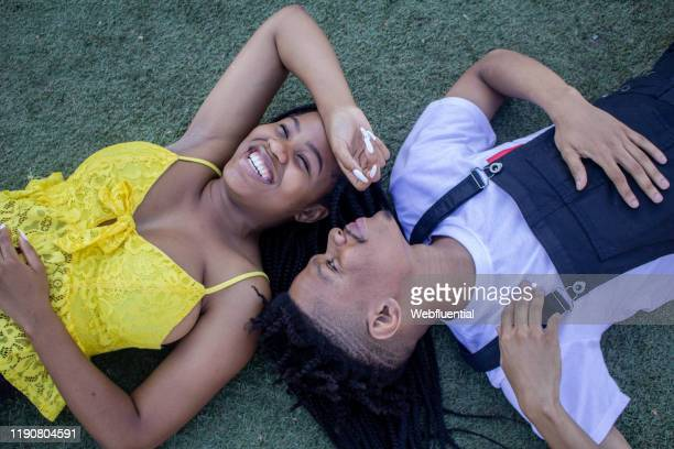 african couple lying on grass - webfluential stock pictures, royalty-free photos & images