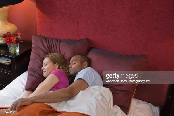african couple sleeping in bed - abbracciarsi a letto foto e immagini stock