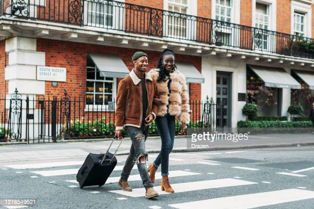 african couple traveling for a short city break - suitcase stock pictures, royalty-free photos & images