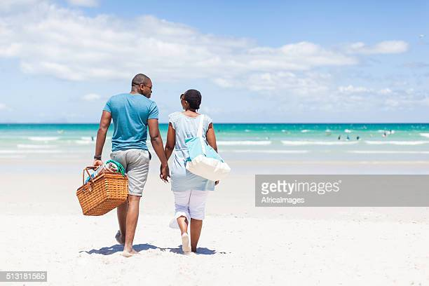 African couple walking on the beach holding hands