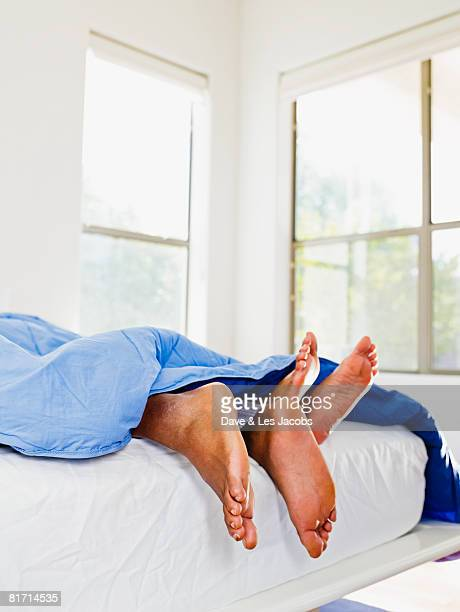 african couple's feet in bed - male feet stock photos and pictures