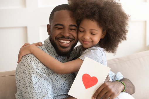African dad embracing daughter holding greeting card on fathers day 1158625150