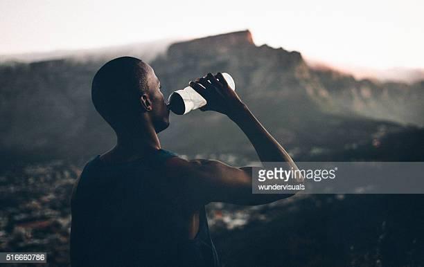 African decent athlete drinking water after a fitness achievemen