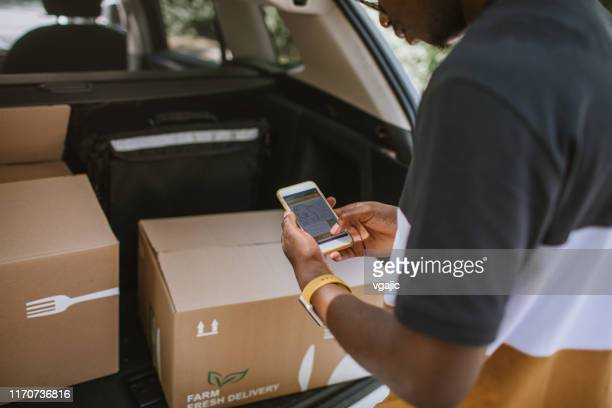 african delivery man checking delivery address in the car trunk - car trunk stock pictures, royalty-free photos & images