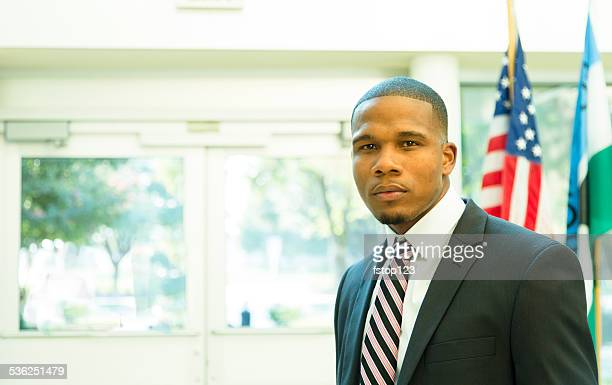 African descent attorney, politician in courthouse building. American flag. Suit.