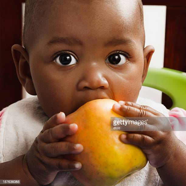 african descent baby girl eating apple, bib, high chair