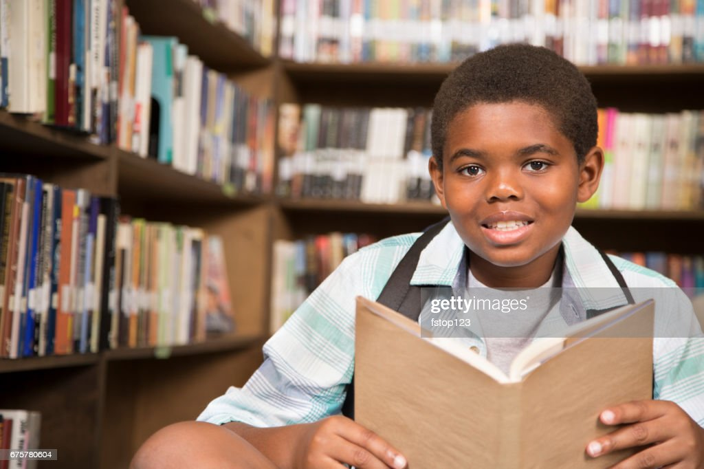 African Descent Boy In School Library Reading Book Stock