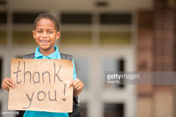 African descent boy, student holds 'thank you' sign. School. Education.