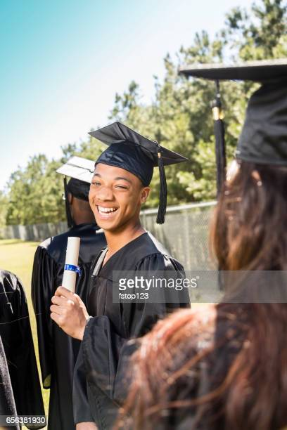 African descent college, high school student waits at graduation.