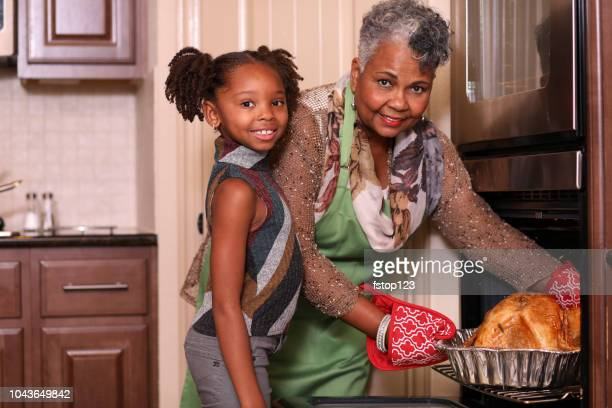 african descent family in home kitchen cooking thanksgiving dinner. - black family dinner stock photos and pictures