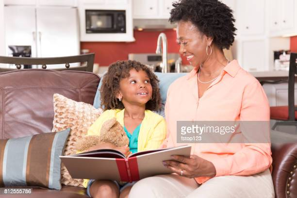 African descent family reading books together at home.